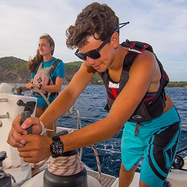 Teens sailing boat on summer sailing adventure program