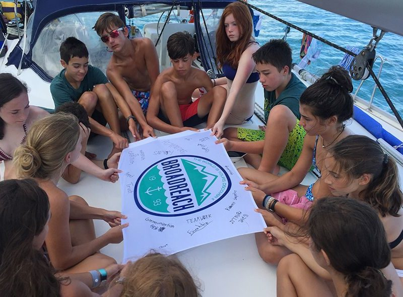 Teens with Broadreach flag on sailing program for middle school students