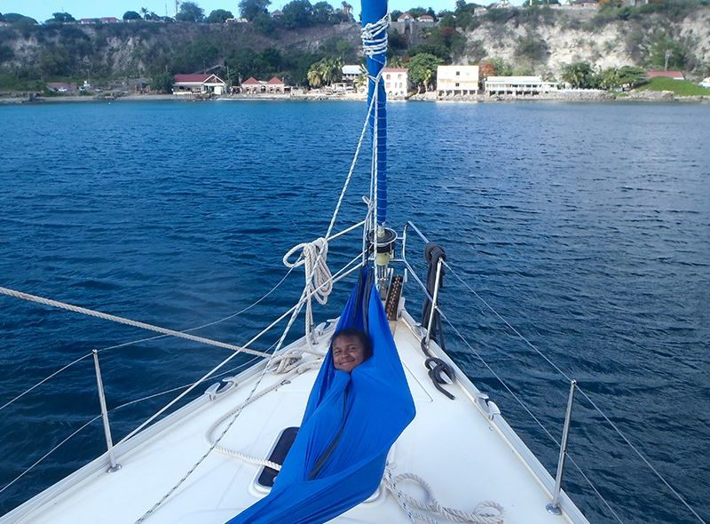 Student in hammock on sailboat on summer sailing program for teenagers