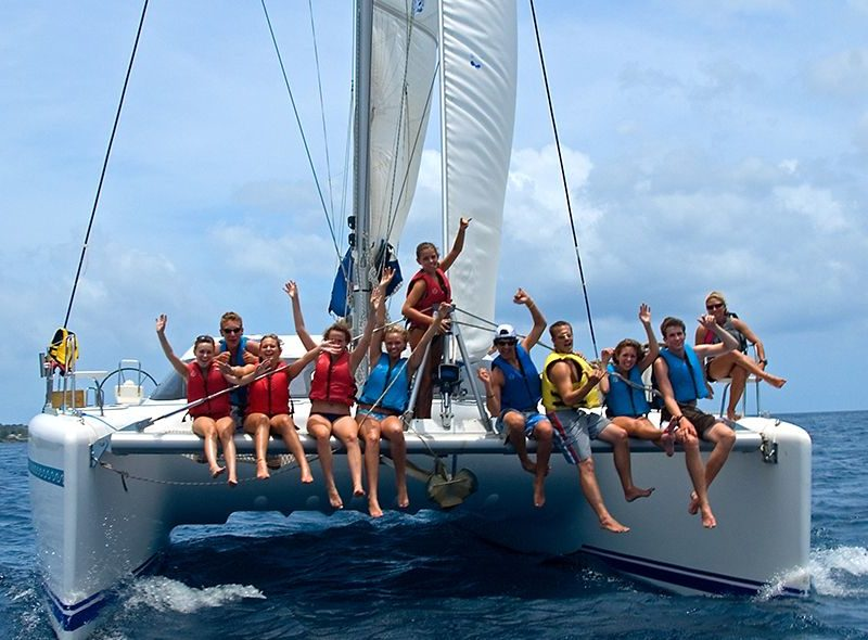Teens sitting on bow on catamaran on summer sailing camp
