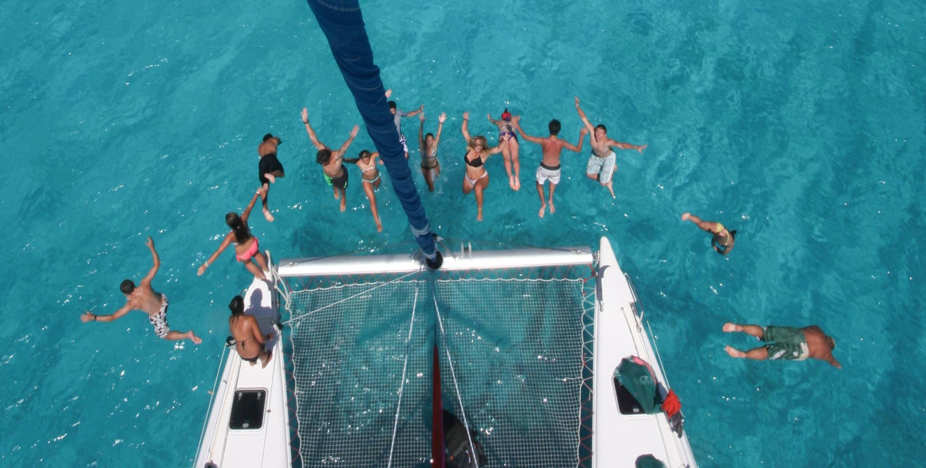 summer programs for teenagers showing teens jumping off boat