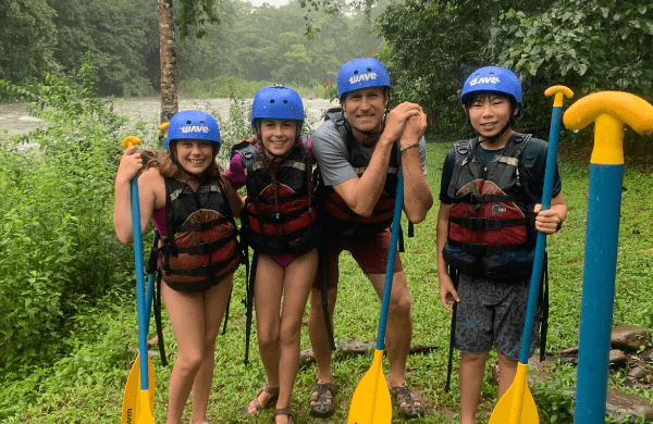 Educator and group of pre-teen students holding kayak paddles in Costa Rica on custom study abroad program